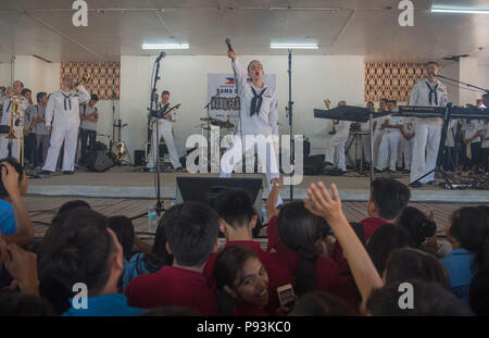 180710-N-OU129-156 SAN FERNANDO CITY, Philippines (July 10, 2018) Members of the U.S. Navy 7th Fleet Band preform for local students at La Union High School as a part of Maritime Training Activity (MTA) Sama Sama 2018. The week-long engagement focuses on the full spectrum of naval capabilities and is designed to strengthen the close partnership between both navies while cooperatively ensuring maritime security, stability and prosperity. (U.S. Navy photo by Mass Communication Specialist 2nd Class Joshua Fulton/Released) - Stock Photo