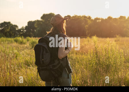 Young woman with tourist backpack in field. Female person looking at sunset in high grass of beautiful rural area in summer - Stock Photo