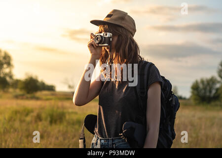 Young female tourist taking photo at hiking trip. Woman with backpack stands at sunset and photographs beautiful rural area - Stock Photo