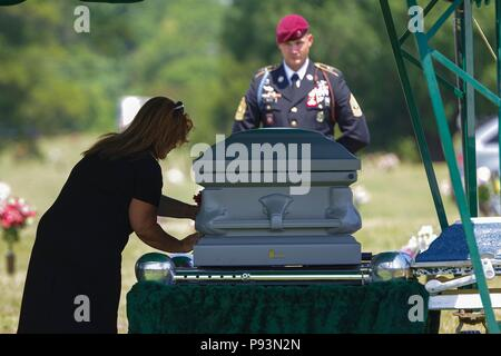 A family member of retired 1st Sgt. Harold Eatman, left, places a flower on his casket at Sharon Memorial Park in Charlotte, North Carolina on July 11 as 1st Sgt. James Miller, right, of Company, B, 2nd Battalion, 505th Parachute Infantry Regiment looks on.  Eatman was a member of the 505th PIR during World War II, making combat jumps into Sicily, Salerno, Normandy and Holland.  Eatman passed away earlier in July at the age of 102. - Stock Photo