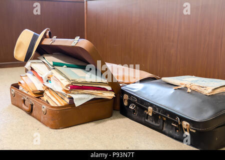 Straw hat is hanging on edge, of old fashioned suitcase made from leather, who is full of folders, papers and documents, overloaded. - Stock Photo