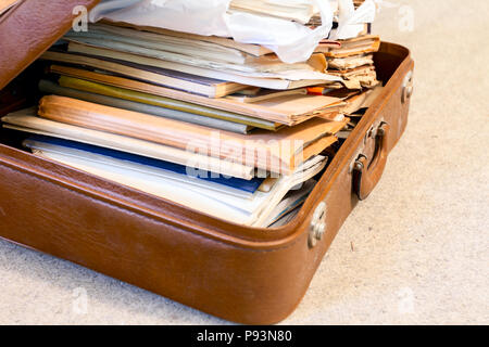 Old fashioned suitcase made of leather is full of folders, papers and documents, overloaded. - Stock Photo