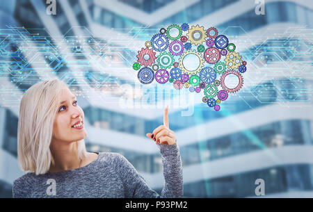 Portrait of smiling woman pointing finger up showing a gear brain hologram. Future technology artificial intelligence. Human logic and emotions concep - Stock Photo