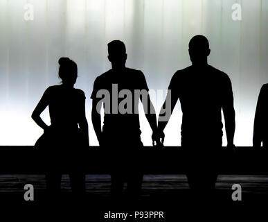 Blurry silhouettes of three young friends students walking in front of the modern building in the black and white night - Stock Photo