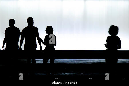 Blurry silhouettes of three young friends students and a boy is looking at a new girl with curly hair standing alone in the black and white night - Stock Photo