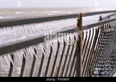 metal fence covered with icicles, icy iron fence - Stock Photo