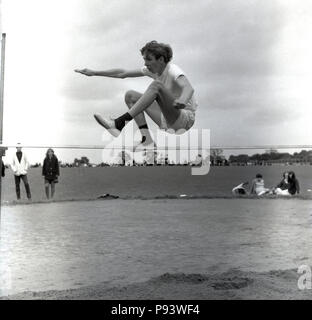 1960s, historical, in mid-air, a teenage boy leaping or jumping over a horizontal high jump bar at a school sports day, England, UK. - Stock Photo