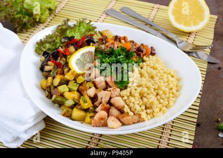 Delicious oriental salad tabbouleh. Couscous with fried vegetables and chicken on a white plate. Traditional Lebanese appetizer. - Stock Photo