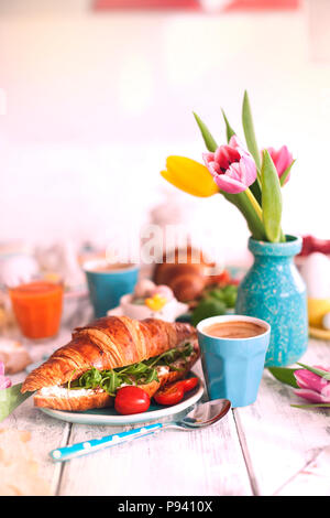 Vintage photo. A family breakfast of croissants with arugula and cheese and aromatic coffee, eggs of different colors. Bouquet of Tulips. - Stock Photo