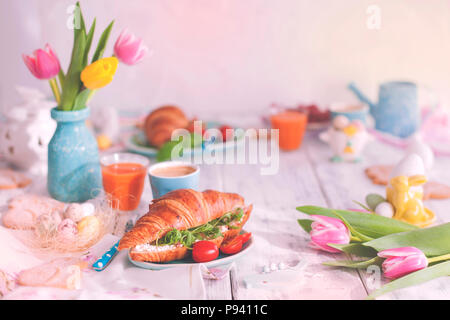 Vintage photo. A family breakfast of croissants with arugula and cheese and aromatic coffee, eggs of different colors. Bouquet of Tulips - Stock Photo