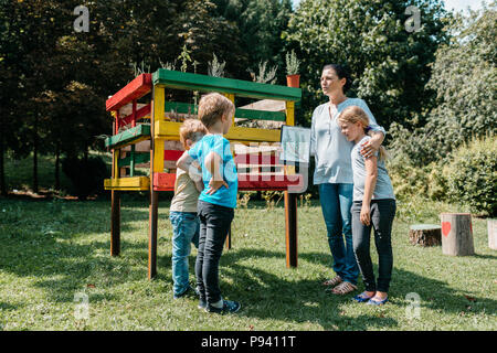 Teacher explaining an environmental topic about herbs to a small group of primary students. Outdoor learning - children discussing with a teacher. - Stock Photo