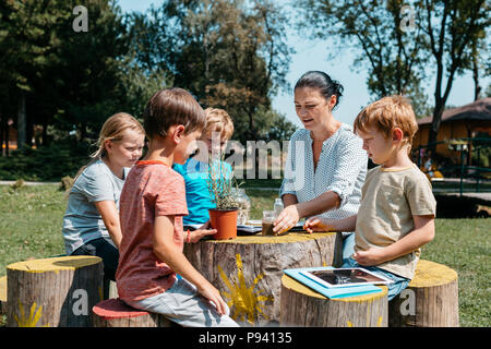 Group of schoolchildren having a lesson outside in a park. Children sitting around a wooden table and learning together with a teacher in the garden. - Stock Photo
