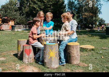 Group of young schoolchildren having a lesson outside in a park. Young primary students exploring herbs through their senses in a garden. - Stock Photo