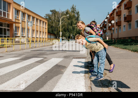 Schoolmates at a crosswalk looking right and left before crossing. Children at a zebra crossing looking around and trying to cross a road. - Stock Photo