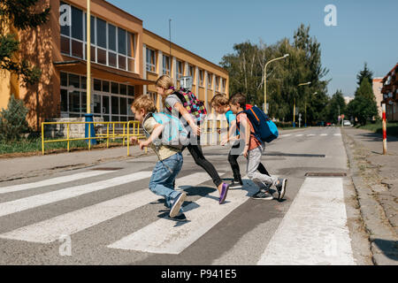 School children running across a street at a crosswalk. Group of primary students rushing to school. - Stock Photo