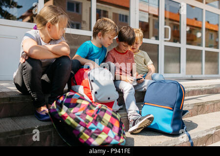 Children sitting outside school playing with a mobile. Group of young students sitting on stairs outside school browsing a phone. - Stock Photo