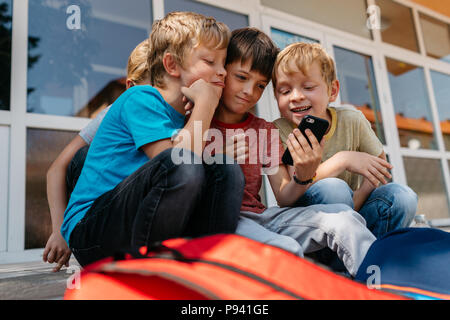 Children with a cell phone taking a selfie outside of school. Group of elementary students having fun playing with a mobile. - Stock Photo