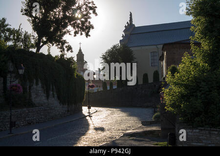 Photo of old cozy paving stone street in the sunny summer morning and backlight. - Stock Photo
