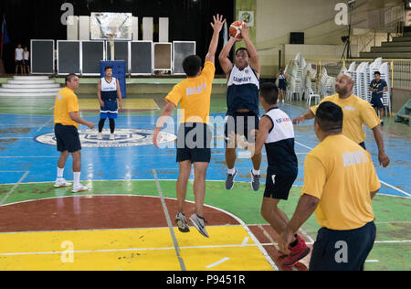 180709-N-OU129-638 SAN FERNANDO CITY, Philippines (July 9, 2018) U.S. Navy sailors play basketball with Philippine Navy sailors at St. Louis College as a part of Maritime Training Activity (MTA) Sama Sama 2018. The week-long engagement focuses on the full spectrum of naval capabilities and is designed to strengthen the close partnership between both navies while cooperatively ensuring maritime security, stability and prosperity. (U.S. Navy photo by Mass Communication Specialist 2nd Class Joshua Fulton/Released) - Stock Photo