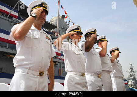 180711-N-TB177-1031 MANAMA, Bahrain (July 11, 2018) Officers salute during a change of command ceremony for the Avenger-class mine countermeasures ship USS Gladiator (MCM 11) on Naval Support Activity Bahrain. Gladiator is forward deployed to the U.S. 5th Fleet area of operations in support of naval operations to ensure maritime stability and security in the Central region, connecting the Mediterranean and the Pacific through the western Indian Ocean and three strategic choke points.  (U.S. Navy photo by Mass Communication Specialist 2nd Class Kevin J. Steinberg/Released) - Stock Photo