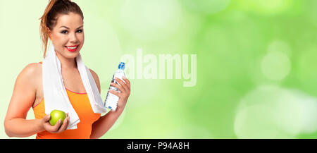 Healthy and Fitness lifestyle banner - beautiful young woman in sportswear with towel, water and green apple on a abstract fresh green background. - Stock Photo