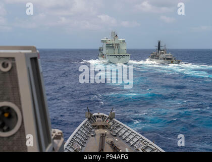 180711-N-YR245-0518 PACIFIC OCEAN (July 11, 2018) Ticonderoga-class guided-missile cruiser USS Lake Champlain (CG 57) approaches Royal Canadian Navy replenishment vessel MV Asterix with Chilean frigate CNS Almirante Lynch (FF 07) alongside at a replenishment-at-sea approach training during Rim of the Pacific (RIMPAC) exercise, July 11. Twenty-five nations, 46 ships and five submarines, and about 200 aircraft and 25,000 personnel are participating RIMPAC from June 27 to Aug. 2 in and around the Hawaiian Islands and Southern California. The world's largest international maritime exercise, RIMPAC - Stock Photo