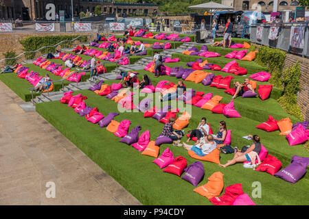People relaxing,Colourfull Sag Bags,Beside,Regents Canal,Granary Square,Kings Cross,London,England - Stock Photo