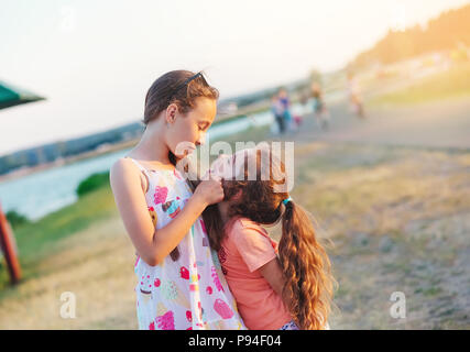 Two Happy little girls having fun and embracing  at meadow at summer day - Stock Photo