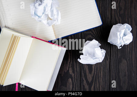 White note pad on a wooden table. near the notepads lies lot crumpled paper. - Stock Photo