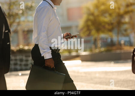 Businessman using mobile phone while commuting to office. Busy office going person walking on street carrying his office bag looking at his mobile pho - Stock Photo