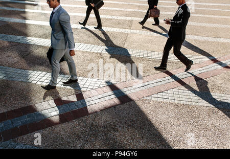Men commuting to office in the morning carrying office bags. Businessmen in a hurry to reach office walking on city street with some using their mobil - Stock Photo