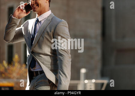 Businessman talking over mobile phone while walking to office in the morning. Man walking on city street to office busy talking on his mobile phone. - Stock Photo