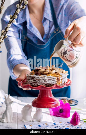 A woman and a cake of thin pancakes with white cream and nuts. Milkman with flowers in the hands of the girl. Spring fresh flowers. Breakfast in the morning. Card - Stock Photo