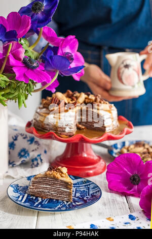A woman and a cake of thin pancakes with white cream and nuts. Milkman with flowers in the hands of the girl. Spring fresh flowers. Breakfast in the morning. Card. - Stock Photo
