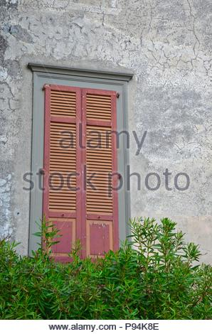 Closed window in a medieval building near Lake d'Iseo in Lombardy, Italy, balcony, conifers, wall, scene, background, iron, grey, red, green, daylight - Stock Photo