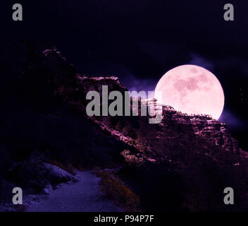 Surreal scenery with giant full moon over the cliffs at the Grand Canyon. - Stock Photo