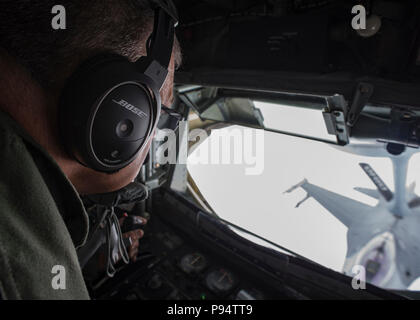 U.S. Air National Guard Tech. Sgt. Mark Perkins, a boom operator with the 121st Air Refueling Wing, Ohio, refuels an F-16 Fighting Falcon with the 158th Fighter Wing, Vermont in the sky over northeastern United States June 27, 2018.  Perkins refueled four F-16 Fighting Falcons during this exercise.  (U.S. Air National Guard photo by Airman 1st Class Tiffany A. Emery) - Stock Photo
