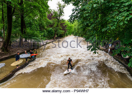 MUNICH-JUNE 14. Surfer man on the Eisbach in the English Garden in Munich on June 14, 2018 in Munich, Germany. - Stock Photo