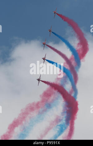 Fairford, UK. 14th July, 2018. The Red Arrow RAF display team at the Royal International Air Tattoo at RAF Fairford in Gloucestershire performing their latest routine to delight the record crowds and yo celebrate the 100th anniversay of the formation of the Royal Air Force. Breathtaking display of of precission flying by these highly trained jet fighter pilots. The display taling place against a clear blue sky and beautiful weather with the continuing heatwave. Credit: Steve Hawkins Photography/Alamy Live News - Stock Photo