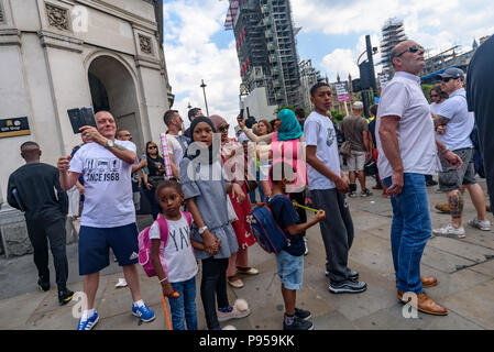 London, UK. 14th July 2018. A man in a Millwall t-shirt stands behind a Muslim family as he photographs the anti-fascist network protesters  on the corner of Parliament Square. The anti-fascist had come to protest against the 'Free Tommy' protests against the jailing of Tommy Robinson for contempt of court for actions which could have stopped the trial of a grooming gang - an offence to which he pleaded guilty.  Peter Marshall/Alamy Live News - Stock Photo