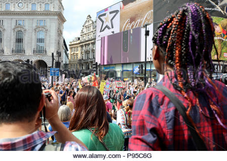 London, Uk. 13th July, 2018. Onlookers watch from the steps of the Eros statue in Piccadilly Circus, central London, at a demonstration to protest against US president Donald Trump Credit: Dominic Dudley/Pacific Press/Alamy Live News - Stock Photo