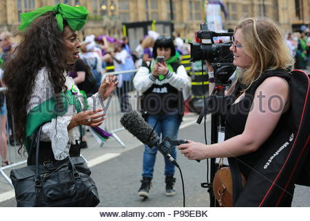 A woman is interviewed at the end of a march to Westminster in honour of suffragettes who won the vote in 1918. - Stock Photo