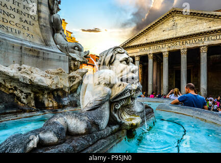 Closeup of the Fontana del Pantheon in the piazza della Rotonda as tourists sightsee with the ancient Pantheon in the background in Rome Italy - Stock Photo