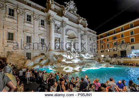 Trevi Fountain in Rome Italy colorfully lit up in the evening with tourists surrounding it on a warm summer evening. - Stock Photo