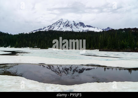 View of Mt. Rainier at Reflection Lakes which are partially frozen, early summer, Mount Rainier National Park, WA, Usa. - Stock Photo