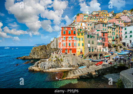 The colorful coastal village, boat lanch and harbor or Riomaggiore Italy on a pretty summer day on the Ligurian Coast. Part of the Cinque Terre - Stock Photo