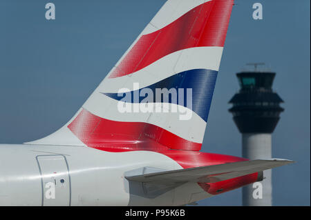 The tailfin of a British Airways Airbus A319-131 taxiing along the runway in front of the control tower at Manchester Airport. - Stock Photo
