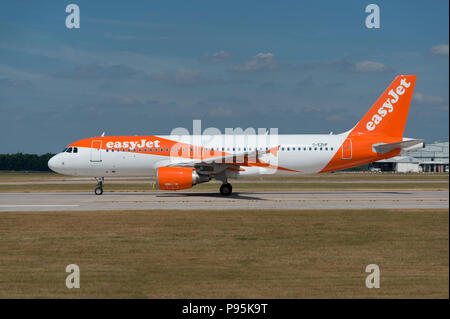 An Easyjet Airbus A319 sits on the runway at Manchester Airport as it prepares to take-off. - Stock Photo