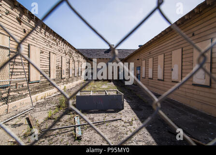 A chainlink fence in front of the abandoned, boarded-up buildings of Naval Station Treasure Island, outside San Francisco, California. - Stock Photo