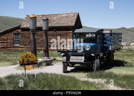 A historic car sits near an old gas station with a Shell sign in the Old West town of Bodie, California. - Stock Photo